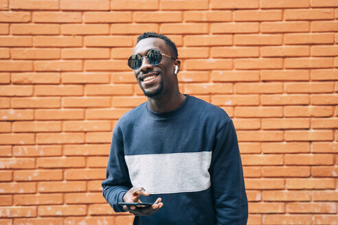 Portrait of happy man wearing sunglasses listening music with wireless earphones and smartphone - OCMF00348