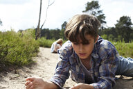 Boy lying on sandy path watching beetle - AMEF00055