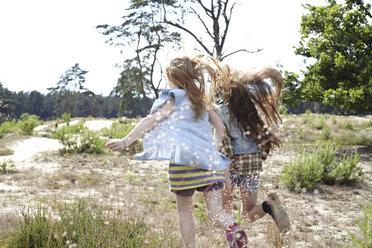 Rear view of two girls running through dune landscape - AMEF00058