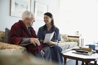 Home caregiver discussing pamphlet with senior man - HEROF33959