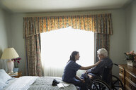 Home caregiver comforting senior man in wheelchair - HEROF33968