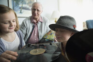 Grandfather and grandchildren listening to old records - HEROF33974