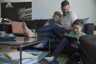 Father and sons relaxing with digital tablets in living room - HEROF34031