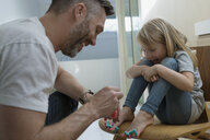 Father painting daughters toenails with nail polish - HEROF34040
