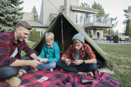 Father and sons playing cards at backyard tent - HEROF34067