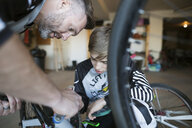 Father and son repairing bicycle - HEROF34070