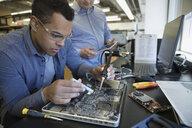 Engineers assembling laptop electronics - HEROF34106