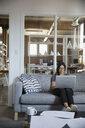 Female designer using laptop on sofa in office - HEROF34121
