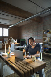 Creative businessman working at laptop in office - HEROF34214
