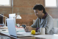 Designer texting with cell phone at laptop in office - HEROF34229