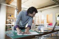 Designer using ruler and bradawl blade on cutting mat in office - HEROF34232