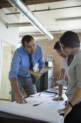 Designers reviewing and discussing plans in office - HEROF34244