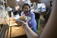 Coworker serving creative businessman birthday donut with sparkler - HEROF34271