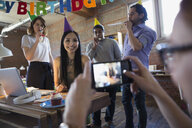 Coworker photographing businesswoman enjoying birthday party in office - HEROF34277