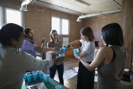 Creative business people celebrating pouring champagne in office - HEROF34280