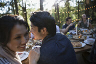 Couple laughing at dining table at wedding reception - HEROF34361