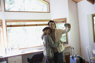 Couple with suitcase taking selfie in cabin - HEROF34370