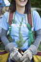 Close up tree planting volunteer holding tree sapling - HEROF34373