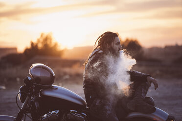 Bearded man with dreadlocks sitting on motorbike at sunset smoking electronic cigarette - OCMF00351