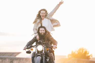 Portrait of happy couple on motorbike - OCMF00354