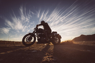 Man on motorbike in nature at sunset - OCMF00357