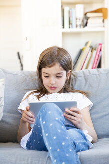 Portrait of little girl sitting on the couch at home using digital tablet - LVF07955