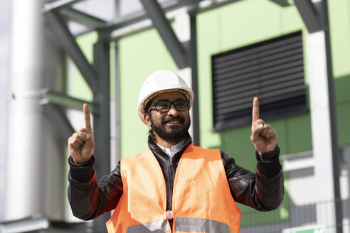 Portrait of construction engineer in front of power station wearing hard hat and safety vest - SGF02343