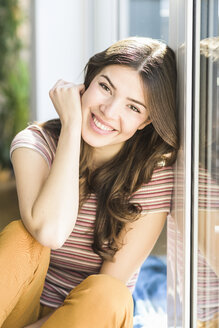 Portrait of smiling young woman sitting at the window at home - UUF17000