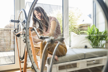 Young woman reparing bicycle at home - UUF17012