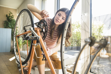 Young woman reparing bicycle at home - UUF17015