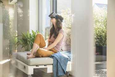 Young woman sitting at the window at home wearing VR glasses - UUF17021
