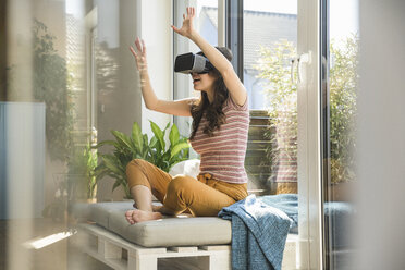 Young woman sitting at the window at home wearing VR glasses - UUF17024