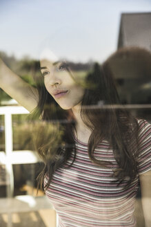 Portrait of pensive young woman behind windowpane - UUF17027