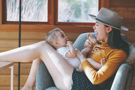 Mpother playing with her baby son in wooden lodge - CMSF00015