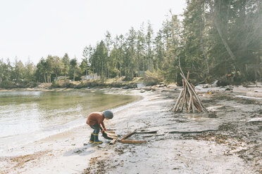Boy playing on a the beach, building a drift wood fort - CMSF00021