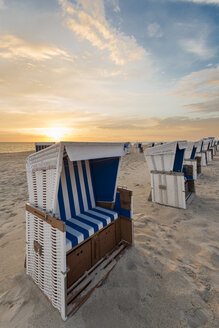 Germany, Sylt, North Sea, sandy beach with hooded beach chairs in sunset - MKFF00487