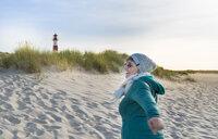 Germany, Sylt, North Sea, woman strolling on sandy beach - MKFF00493