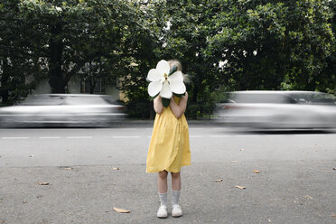 Girl wearing yellow dress hiding her face  behind oversized white magnolia blossom - EYAF00086