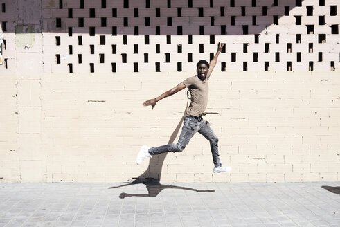 Happy young man jumping in the air - IGGF00959