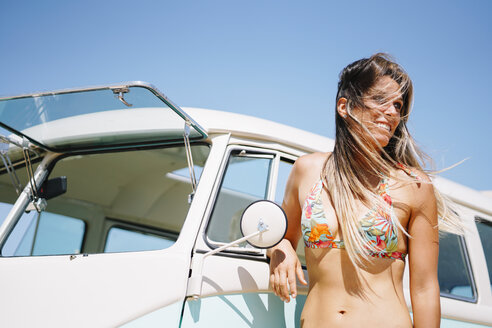 Pretty woman in a bikini leaning against an old transporter - OCMF00359