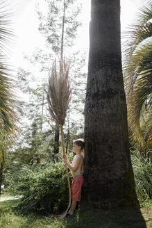 Boy leaning against a palm tree - EYAF00103