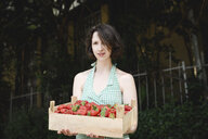 Portrait of woman holding crate with strawberries - EYAF00112