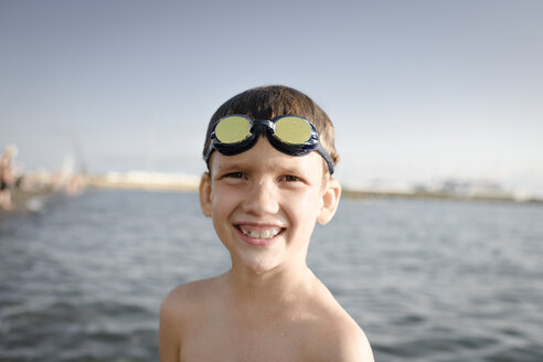 Portrait of happy boy with swimming goggles at the sea - EYAF00115