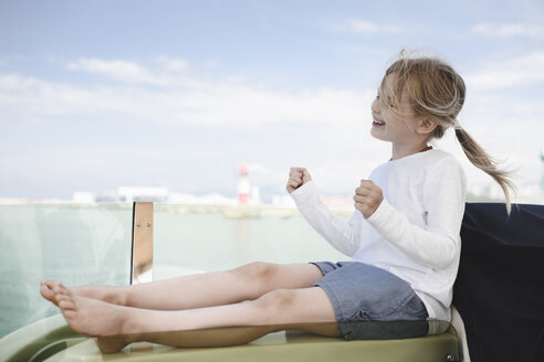 Happy little girl sitting on lounger clenching fists - EYAF00118