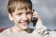 Portrait of happy boy on cell phone - EYAF00121