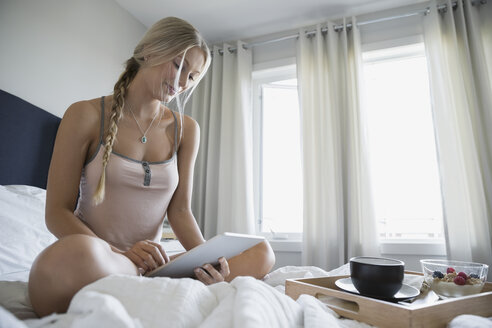 Pensive woman with digital tablet and breakfast bed - HEROF34381