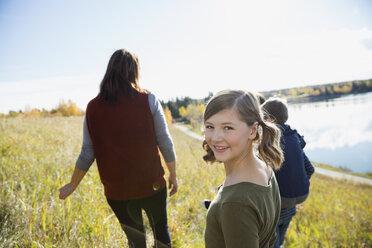 Portrait smiling girl looking over shoulder in sunny field - HEROF34474
