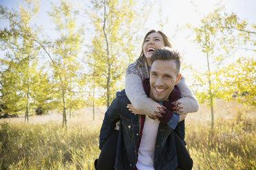 Playful couple piggybacking in sunny field - HEROF34477
