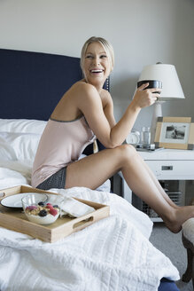 Laughing woman drinking coffee on bed in bedroom - HEROF34480
