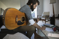 Man with guitar writing music in living room - HEROF34483